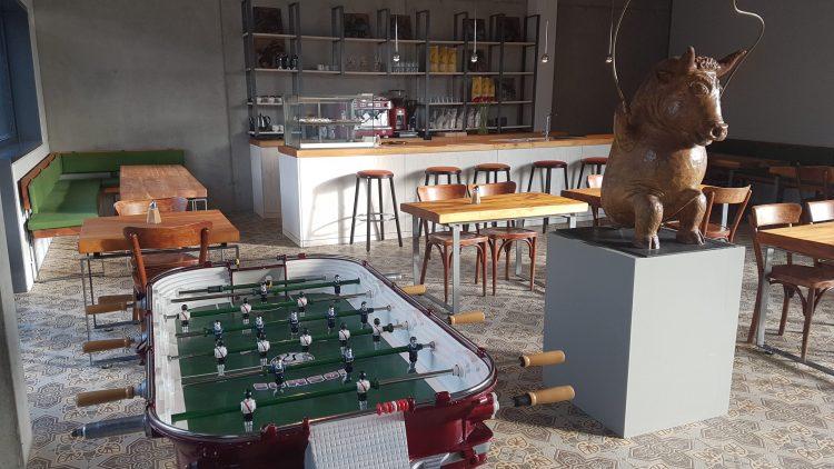 Der hintere Raum ist ein Café mit altem Kicker und seilspringendem Wildschwein.