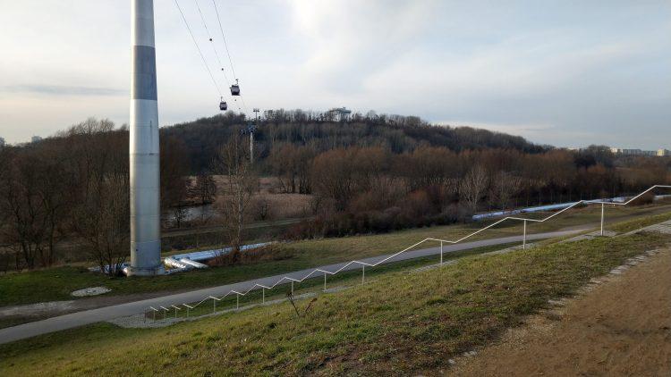 Bewaldeter Hügel mit Seilbahn, im Vordergrund Grashang mit Treppe, dahinter Fluss Wuhle