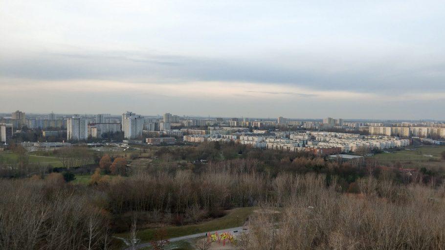 Aussicht von Kienberg auf die Hochhaus- und Neubausiedlung Marzahn, darüber Himmel, davor kahle Laubbäume