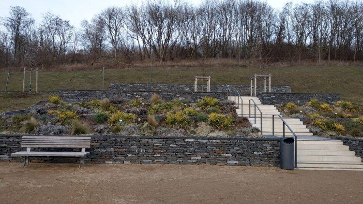 Garten am Hang zwischen Natursteinmauern, davor Bank, im Hintergrund Wiese und kahle Laubbäume