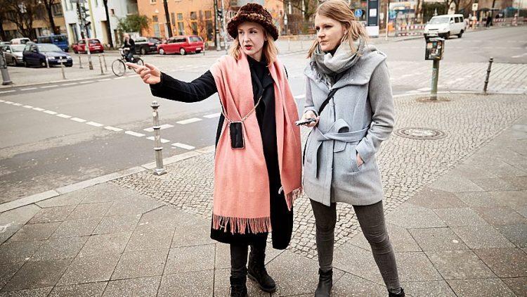 Leslie Clio und die Reporterin stehen im Mantel an einer Kreuzung, Leslie zeigt auf etwas.
