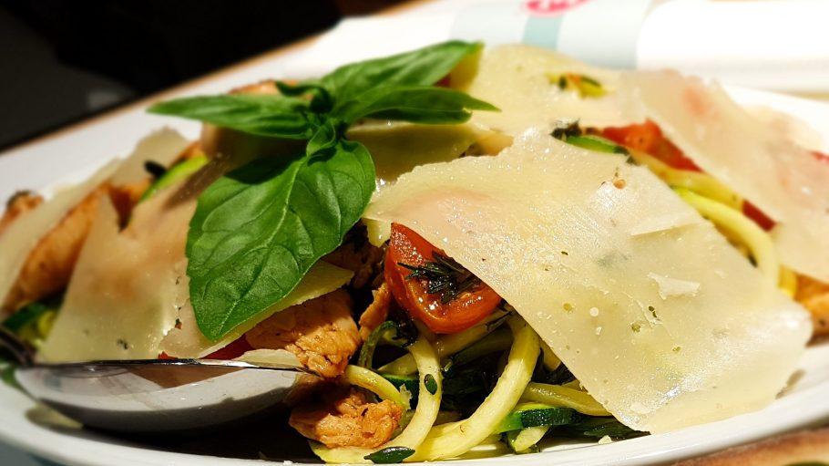 Glutenfreie Zucchini-Spaghetti mit Hähnchen, Cherrytomaten und Parmesanscheiben.