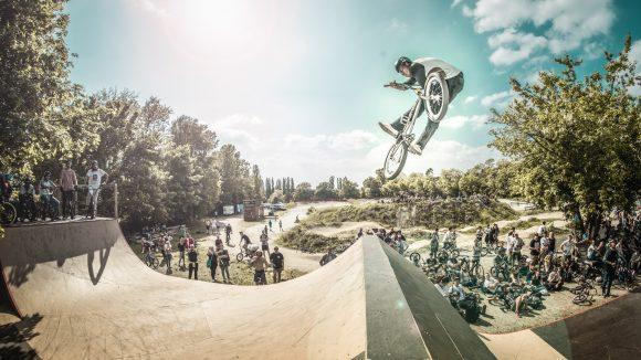 BMX Fahrer auf Rampe im Mellowpark Köpenick im Flug vor Zuschauern.