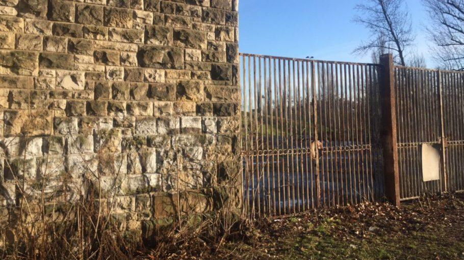 Betonwand und rostiger Zaun