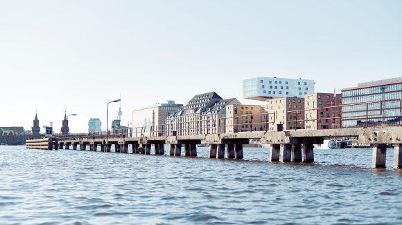 Ein Fluss, die Spree, mit parallel laufendem Steg, Uferhäuser, viele modern, im Hintergrund Oberbaumbrücke
