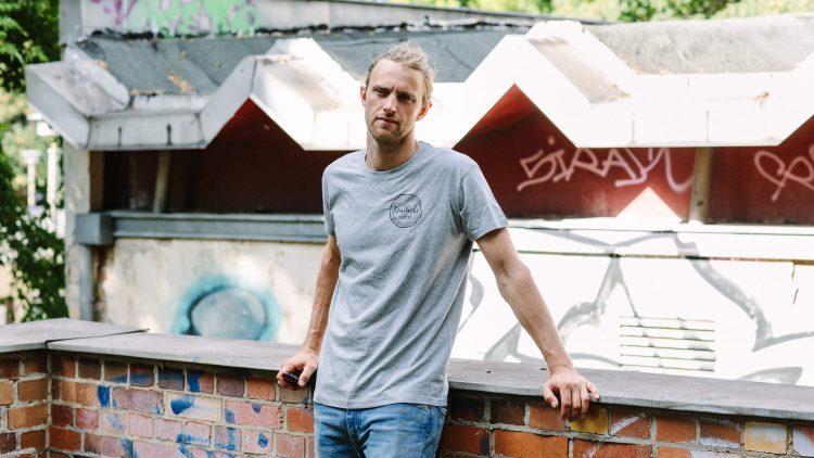 Stacey Kent von Kentholz lehnt mit grauem T-Shirt an einer Mauer.