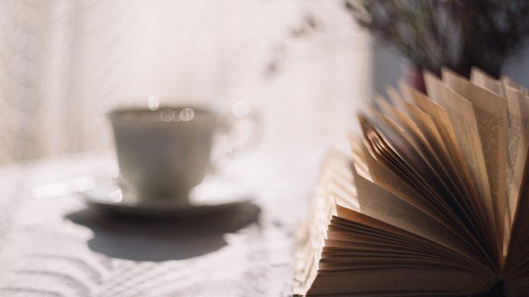 Buch liegt auf einem Tisch, daneben Kaffeetasse.