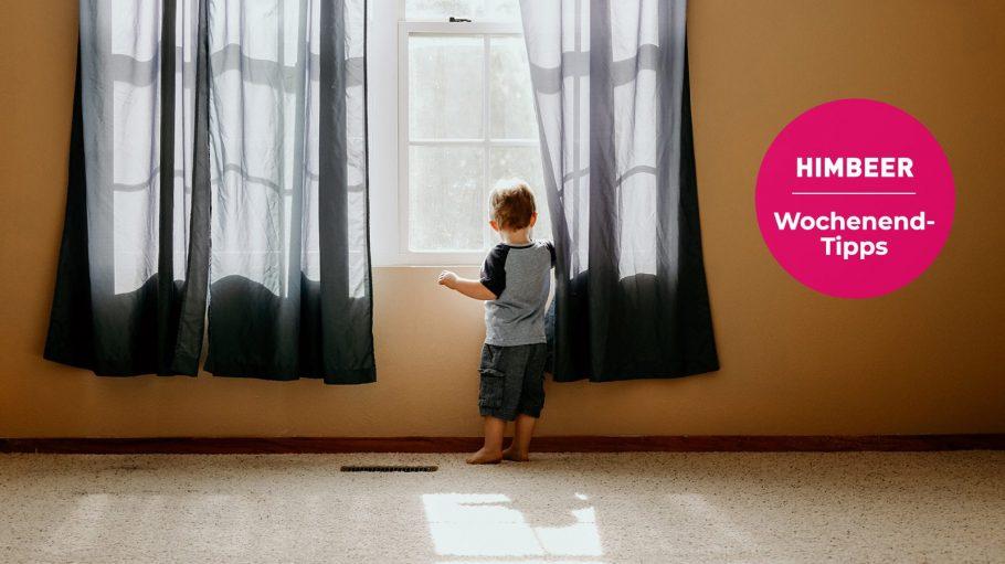 Kleiner Junge guckt aus einem Fenster raus, vor dem dunkle Gardinen hängen