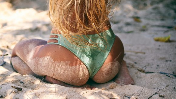 Frauenhintern in Bikinihose im Sand