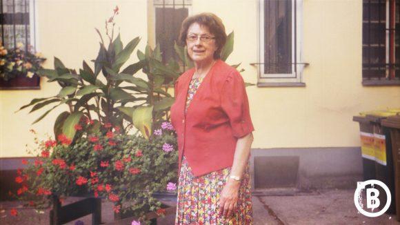 Ältere Frau mit Kleid und rotem Blazer vor Blumen