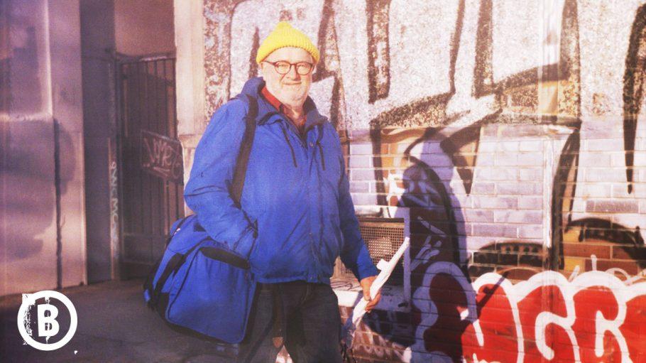 Mann mit blauem Anorak und gelber Pudelmütze vor Graffitiwand