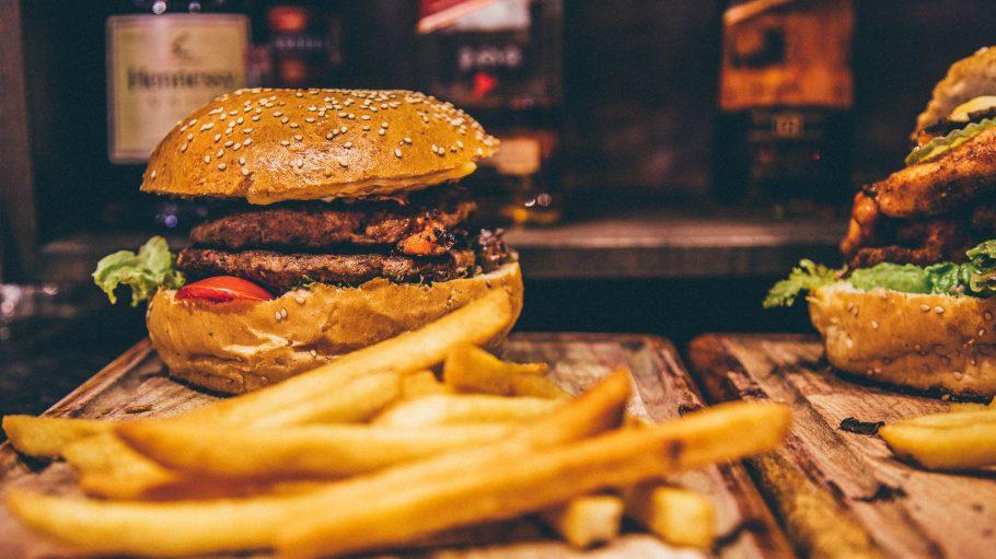 Burger mit Pommes Frites auf einem Holzbrett
