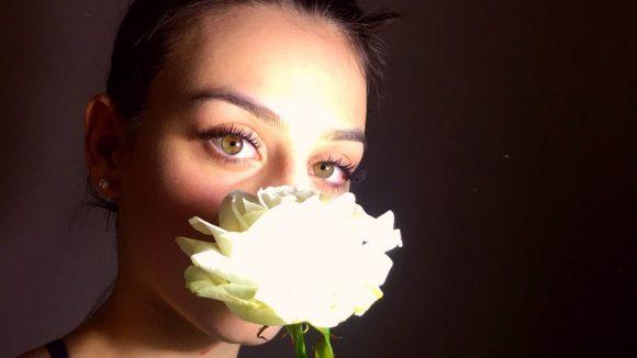 Frau mit Dutt vor einer schwarzen Wand riecht an einer weißern Rose und zelebriert den Augenaufschlag bei Revolver Eyes.