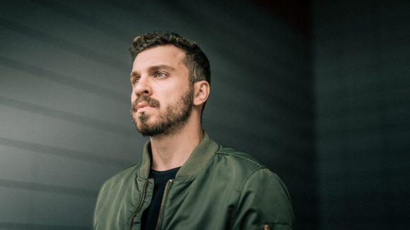 Edin Hasanovic vor einer dunklen Wand.