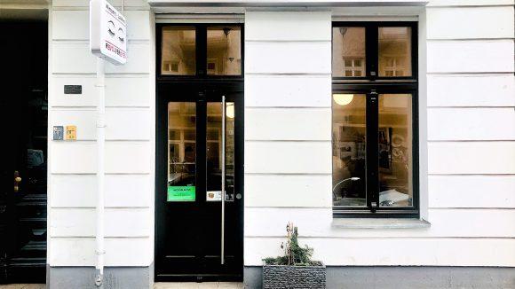 Ladengeschäft im Erdgeschoss in einem Haus mit weißer Fassade in Friedrichshain. Buntes Schild mit der Aufschrift Revolver Eyes über der Eingangstür.