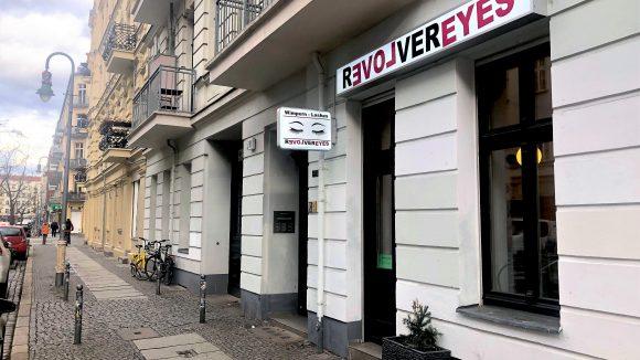 Kosmetikstudio Revolver Eyes in der Mainzer Straße in Berlin. Weiße Fassade vom Altbau im Erdgeschoss mit großem Schild über der Eingangstüre.