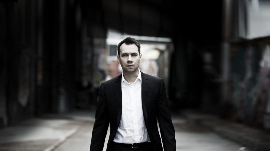 Sebastian Fitzek im dunklen Anzug in einem Hinterhof