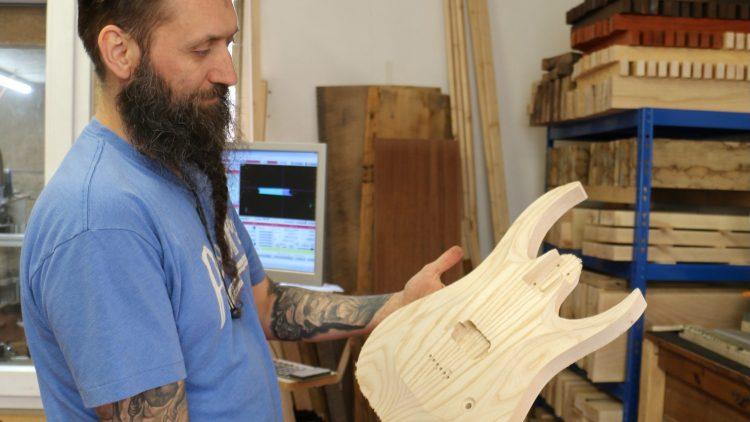 Mann mit Bart hält Gitarrenkörper aus Holz in der Hand
