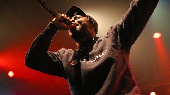 Musiker mit Mikrophone in der Hand und schwarzem Pulli.