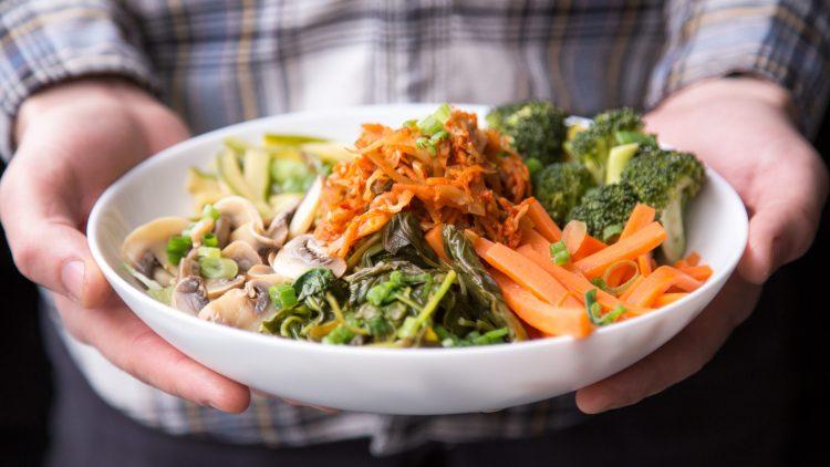Mann mit kariertem Hemd hält einen weißen Teller mit Gemüse in den Händen