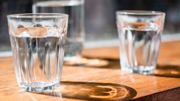Zwei Wassergläser auf einem Holztisch gefüllt mit Berliner Leitungswasser.