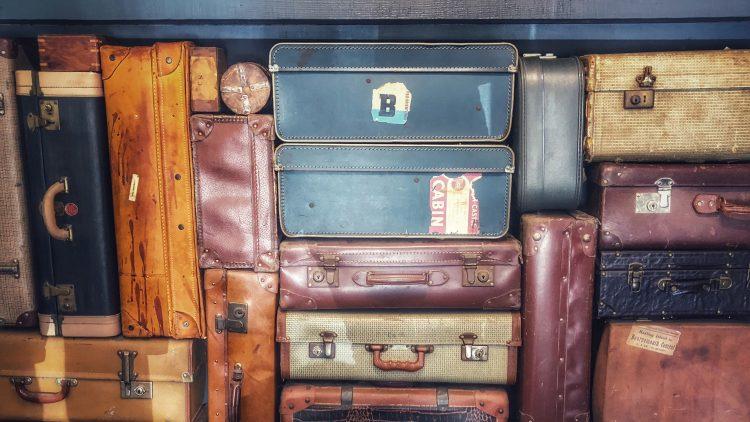 Alt aussehende Koffer verschiedener Farben senkrecht und waagrecht gestapelt