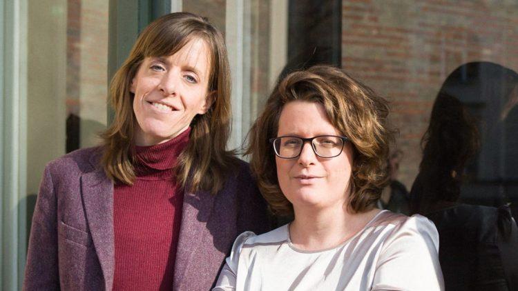 Zwei Frauen mit dunkelblonden Haaren stehen nebeneinander, die linke mit lilanem Blazer und rotem Pullover, die rechte mit Brille und weißem Oberteil: Janika Gelinek und Sonja Longolius
