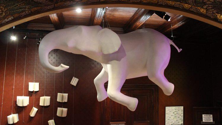 Weiße Elefanten-Plastik hängt an der Decke eines holzgetäfelten Foyers, im Hintergrund aufgeschlagene Bücher an Drähten