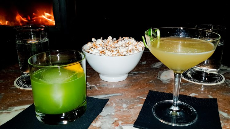 Ein grüner Longdrink Gin Basil Smash, ein gelber longdrink Hemmingways Passion.