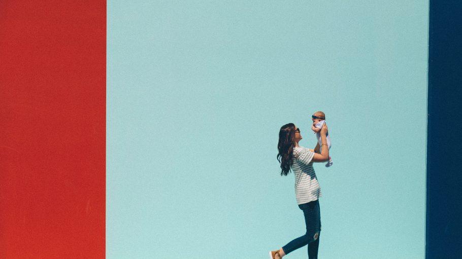Frau mit Baby vor farbenfrohem Hintergrund