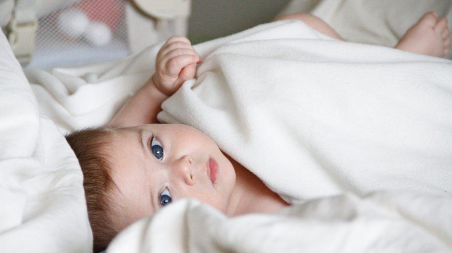 Baby schaut aus einer weißen Decke hervor.