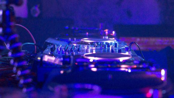 DJ-Mischpult im Fokus, lila Licht, Ränder verschwommen
