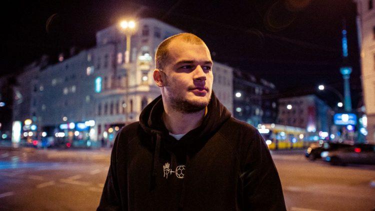 Junger Mann mit kurzen dunkelblonden Haaren und schwarzem Kapuzenpulli steht vor nächtlicher Kreuzung in Berlin (Paul Drux)