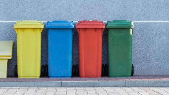 Gelbe, blaue, rote und grüne Mülltonne nebeneinander.