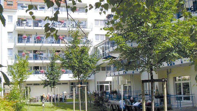 Weißes fünfstöckiges Seniorenheim mit Balkonen, im Vordergrund Garten, einige alte Leute sitzen auf Bänken