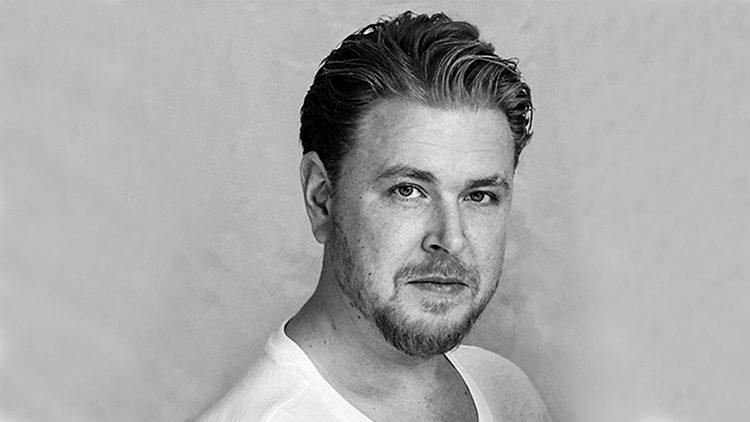 Philip Bondulich, Geschäftsführer Dipl. Kommunikationsdesigner auf einem schwarz-weiß Portrait mit weißem T-Shit vor grauer Wand.