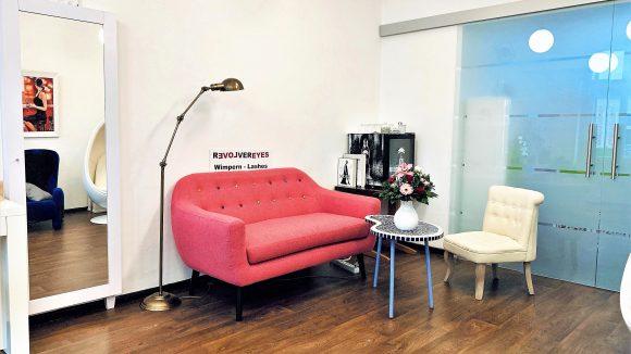 Rosa Couch, Holzboden und weiße Wände im Wartezimmer von Revolver Eyes.