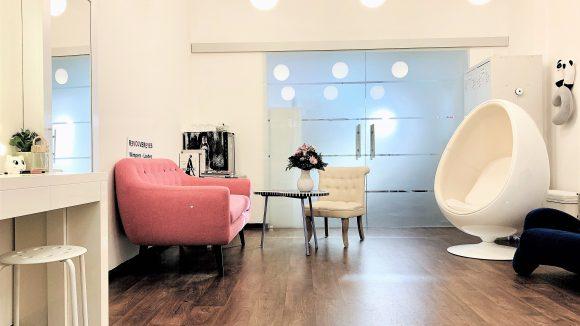 Helles und freundliches Wartezimmer von Revolver Eyes mit warmem Holzboden, weißen Wänden und modernem Sessel.