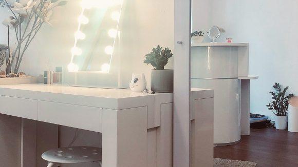 Weißer Tisch mit hellen Lampen, rechts davon ein großer Spiegel am Schminktisch bei Revolver Eyes.