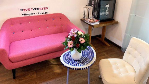 Rosa Couch, blau-gekachelter Kaffeetisch mit Blumen in einer Vase und ein weißer Sessel. Im Hintergrund ein Kühlschrank mit Getränken.