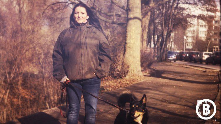 Frau mit Anorak und Hund auf der Straße unterwegs