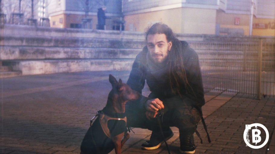Mann mit langen dunklen Rastas in der Hocke mit Hund