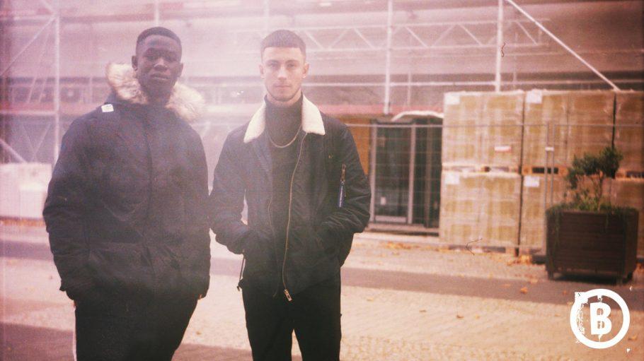 Zwei coole Jungs mit Anorak draußen vor einer Baustelle