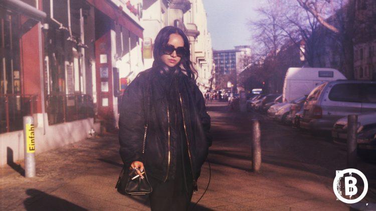 Frau mit Sonnenbrille und Zigarette draußen auf der Straße