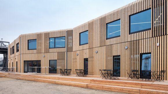 Moderner Bau aus Holz mit Terrasse und großen Fenstern, Coworking-Space