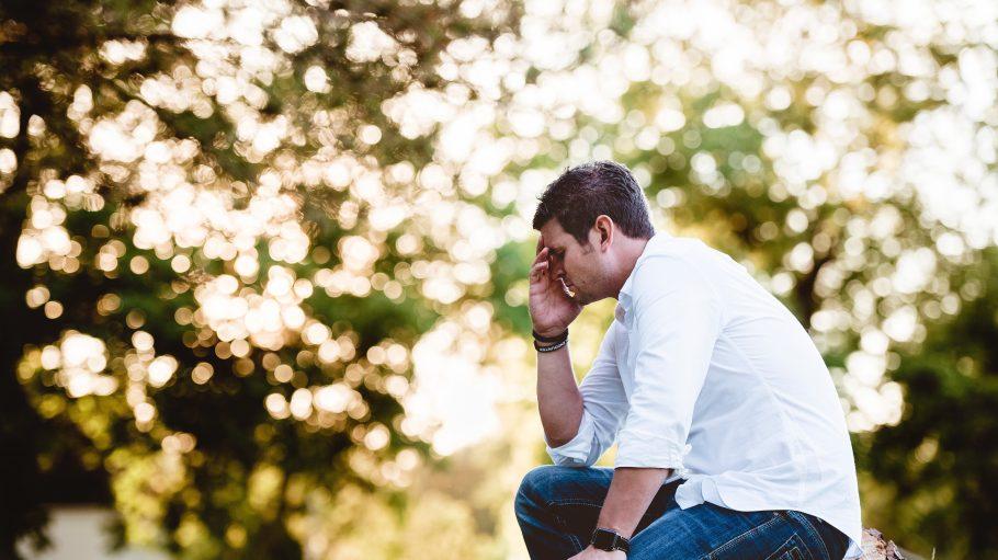 Mann sitzt mit Hand am Kopf im Grünen