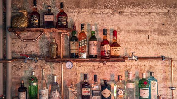 Spirituosen-Flaschen stehen auf Holzregal an industriell aussehender Wand