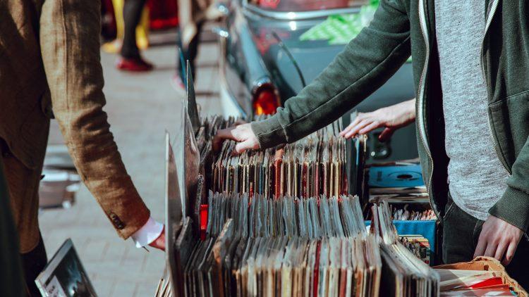 Stand mit Vinyl-Schallplatten auf Flohmarkt, die Arme zweier Männer sind zu sehen, im Hintergrund Auto