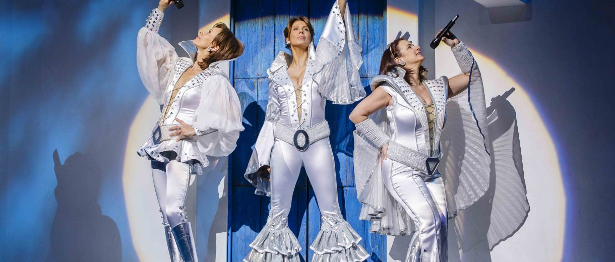 Szenenfoto aus Musical Mamma Mia: die 3 Dynamos in Siebziger Jahre Outfits