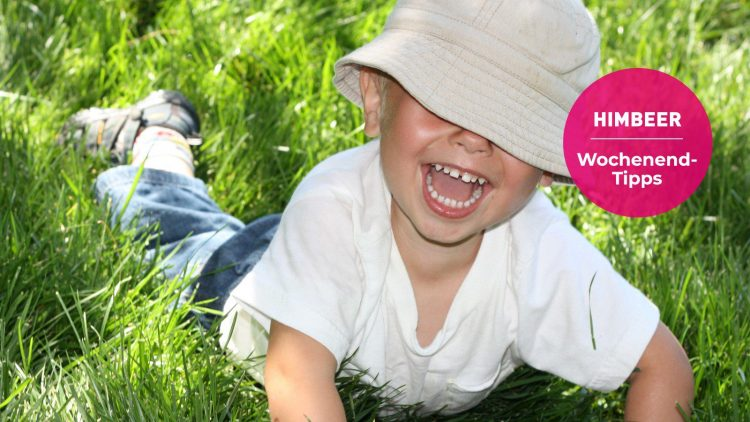 Kleines Kind mit Mütze liegt im Gras und lacht.